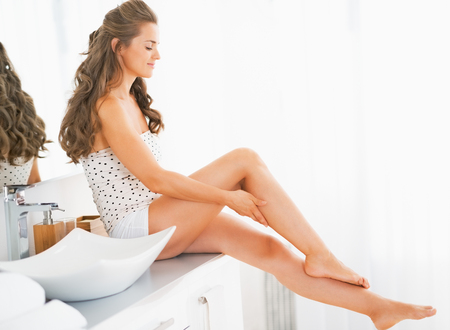 beautiful legs: Happy young woman sitting in bathroom and checking leg skin softness Stock Photo