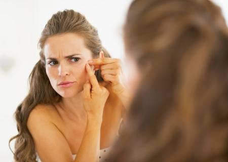 Gefrustreerde jonge vrouw knijpen acne