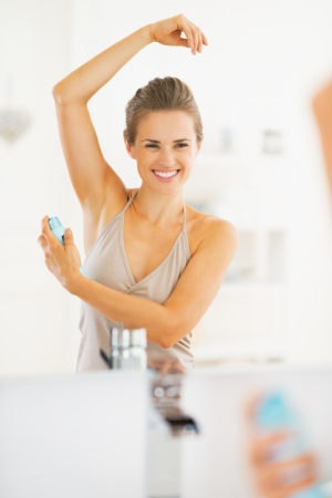 Smiling young woman applying deodorant on underarm