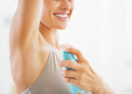 Close-up op de jonge vrouw toepassing deodorant op onderarm
