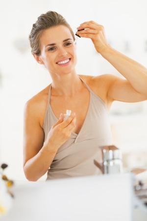 serum: Young woman applying cosmetic serum in bathroom