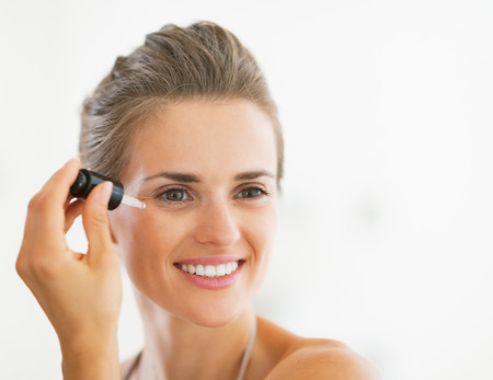hygienics: Portrait of happy young woman applying cosmetic serum Stock Photo