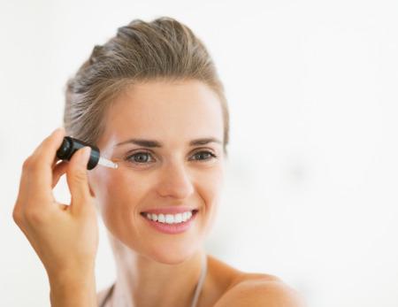 Portret van gelukkige jonge vrouw die cosmetische serum Stockfoto