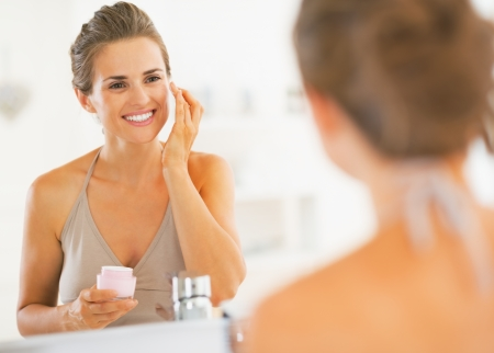 Happy young woman applying cream in bathroom photo