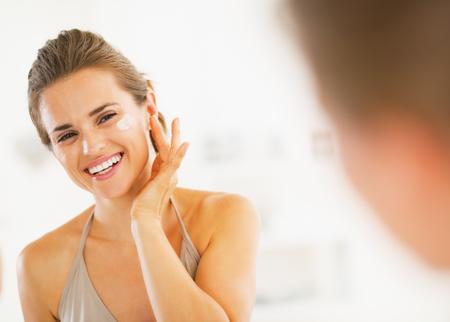 hygienics: Happy young woman applying cream in bathroom