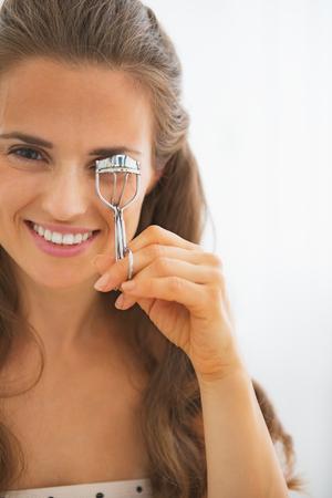 curler: Happy young woman using eyelash curler