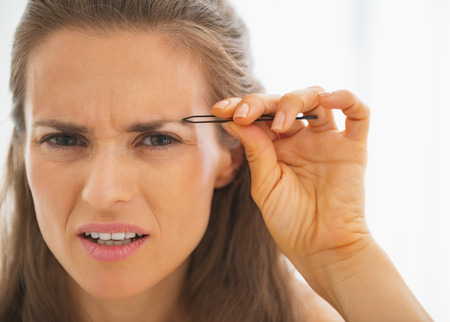 tweezing: Displeased young woman tweezing eyebrows