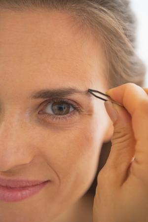 tweezing eyebrow: Closeup on happy young woman tweezing eyebrows
