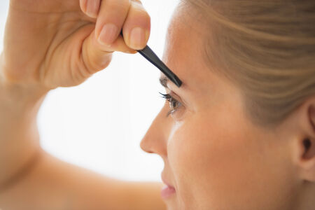 tweezing: Closeup on young woman tweezing eyebrows