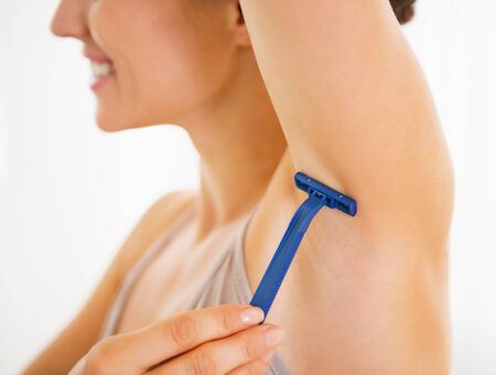 axilla: Closeup on young woman shaving armpit Stock Photo