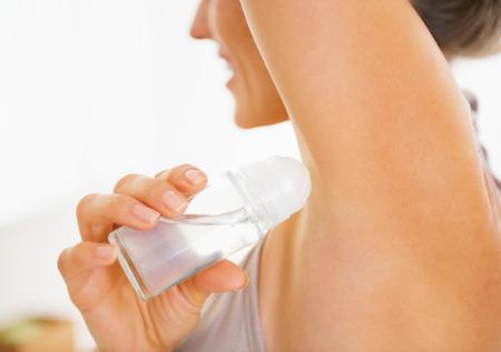 armpit: Primer en la mujer joven aplicar desodorante en las axilas