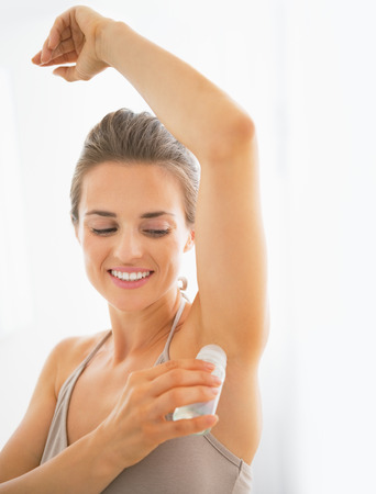 perspiration: Happy young woman deodorant on underarm Stock Photo