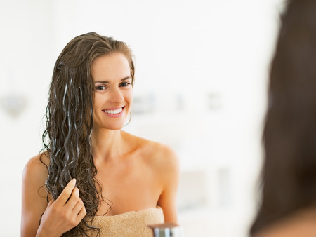 treatment: Happy young woman applying hair mask in bathroom