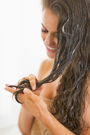 apply: Closeup on happy young woman applying hair mask in bathroom Stock Photo