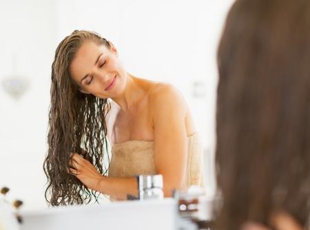 mojar: Mujer joven feliz con el pelo mojado en el baño