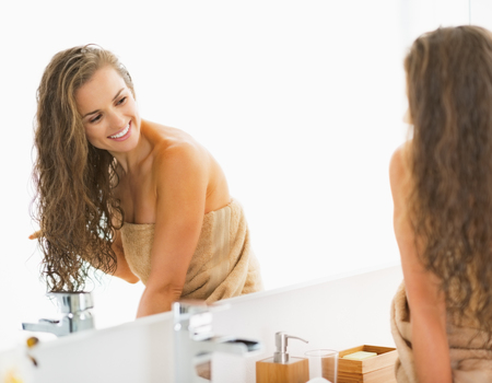 wet hair: Smiling young woman sitting with wet hair in bathroom and looking in mirror