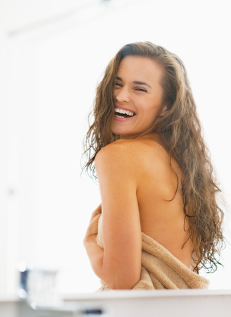 wet hair: Portrait of smiling young woman with wet hair in bathroom Stock Photo