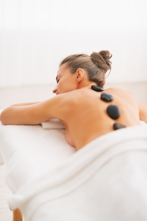 Young woman receiving hot stone massage. rear view photo