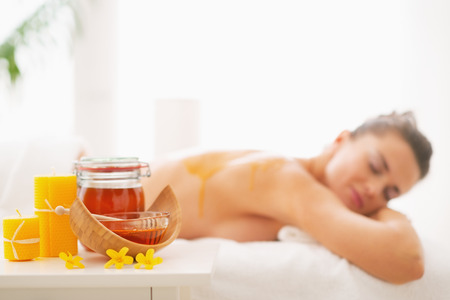 Closeup on honey spa therapy ingredients and young woman in background