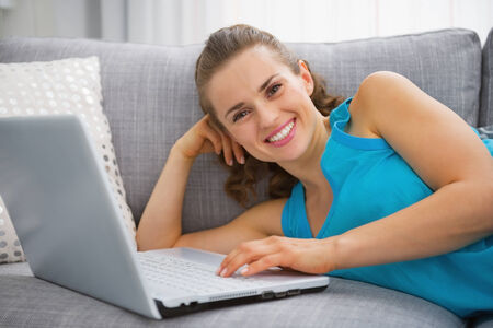 Smiling young woman laying on sofa with laptop