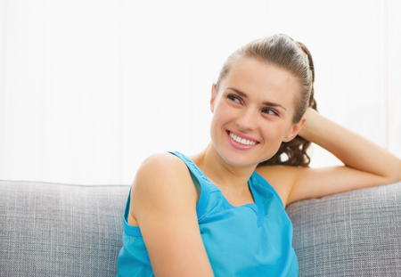 Happy young woman looking on copy space while sitting on couch
