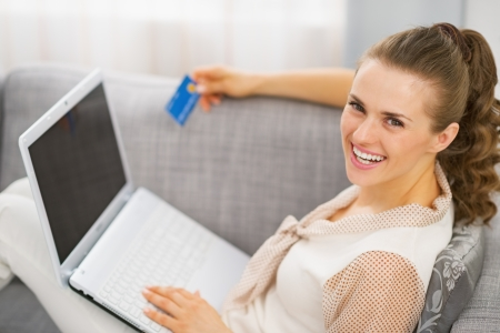 topicality: Portrait of smiling young housewife with credit card and laptop