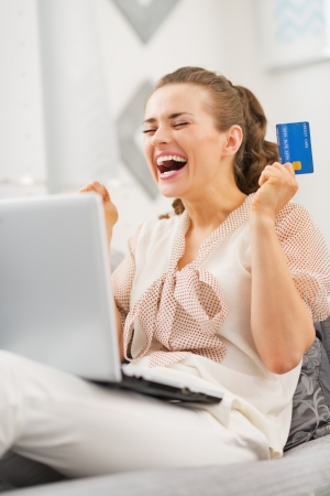 Happy young woman with credit card and laptop rejoicing Stock Photo - 25398224