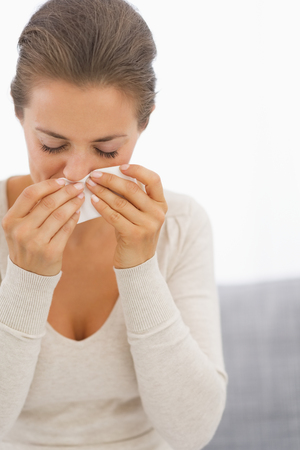 Young woman blowing nose Stock Photo - 25398239