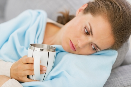 Displeased young woman with flu having cup of hot beverage photo