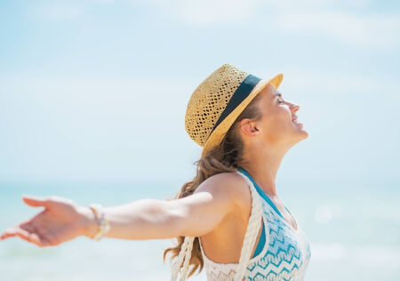 rejoicing: Happy young woman in hat and with bag rejoicing on beach