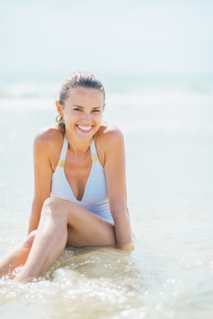 Smiling young woman in swimsuit enjoying sitting in sea water photo
