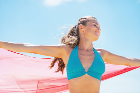 Happy young woman with parero rejoicing on beach Stock Photo