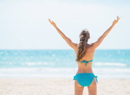 rejoicing: Portrait of smiling young woman rejoicing on beach. rear view Stock Photo