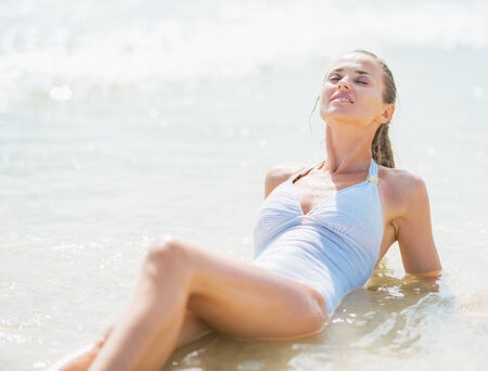 Happy young woman in swimsuit enjoying laying in sea water photo