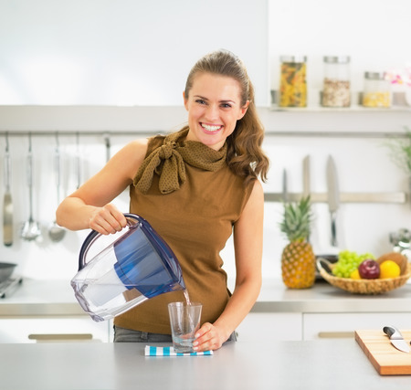 jugs: Happy young housewife pouring water into glass from water filter pitcher