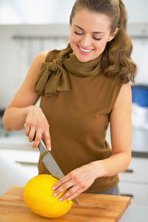 Happy young housewife cutting melon photo