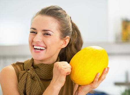 Smiling young housewife checking ripeness of melon photo