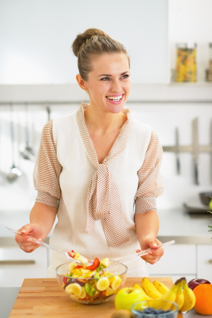 Smiling young housewife making fruit salad in kitchen photo