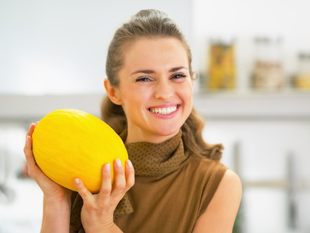 Happy young housewife holding melon photo
