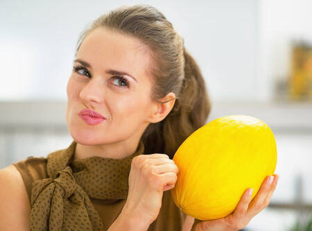 Happy young housewife checking ripeness of melon photo