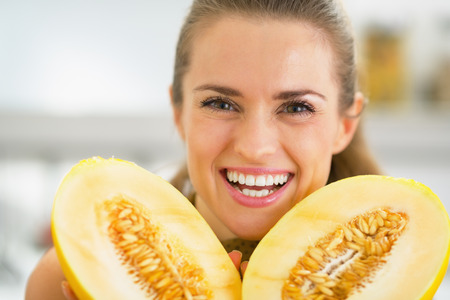 Smiling young woman showing melon photo
