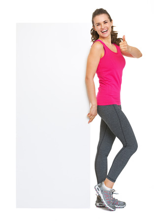 Full length portrait of fitness young woman showing blank billboard and thumbs up Stock Photo - 25628334
