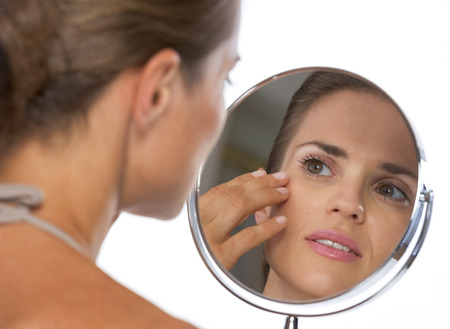 aging face: Young woman looking in mirror Stock Photo