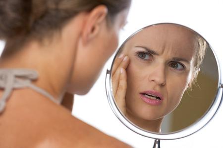 Bezorgd jonge vrouw die in spiegel