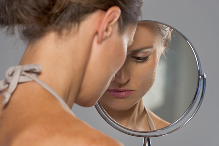 upset woman: Stressed young woman looking in mirror Stock Photo