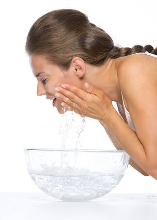 Profile portrait of happy young woman washing face in glass bowl with water