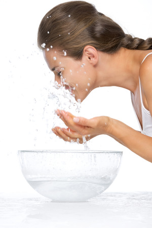 limpieza de cutis: Retrato de perfil de joven, mujer, cara de lavado en un recipiente de vidrio con agua Foto de archivo