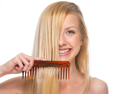 Happy young woman combing hair photo