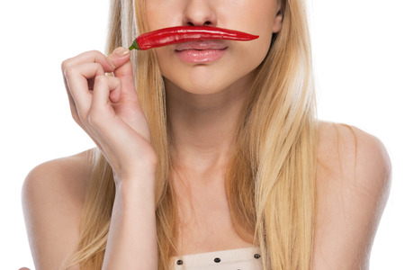Closeup on young woman with red chili pepper photo