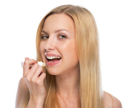 Young woman using hygienic lipstick